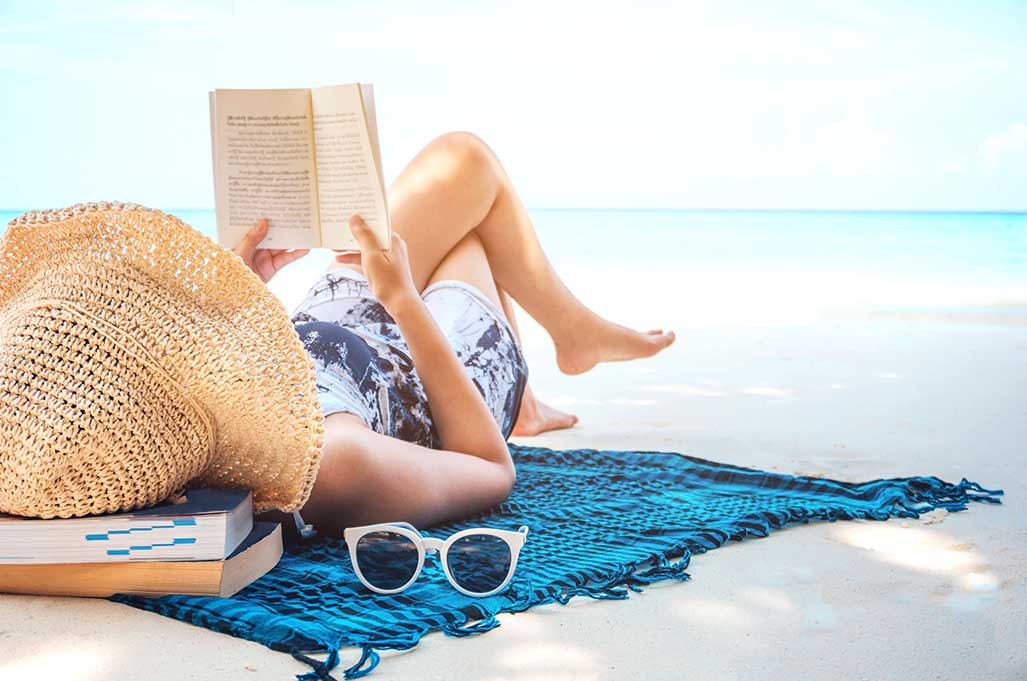 Women reading a book on the beach
